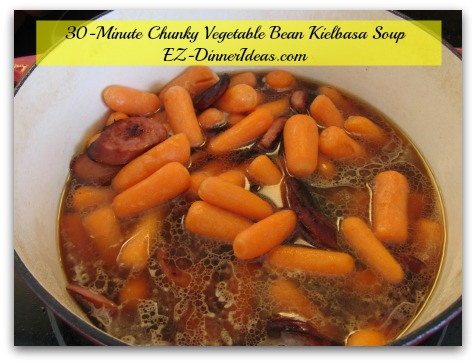 30-Minute Chunky Vegetable Bean Kielbasa Soup - Add carrots, broth/stock, tomatoes with juice, spices and herbs