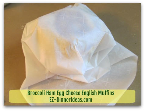 Broccoli Ham Egg Cheese English Muffins - Wrap each sandwich individually with parchment paper - step 2