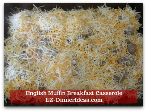 English Muffin Breakfast Casserole - Spread pre-shredded cheddar cheese evenly on top of muffin and sausage pieces.