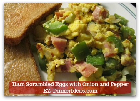 Serve ham scrambled eggs with onion and pepper with hearty wheat toasts