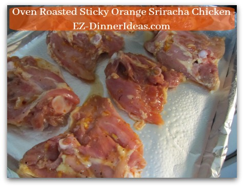 Oven Roasted Sticky Orange Sriracha Chicken - Skin side down on a lined baking sheet and roast