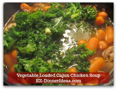 Kale Chicken Soup | Vegetable Loaded Cajun Chicken Soup - Stir in kale and use a spatula to press the vegetables down into the soup.