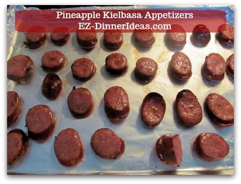 "Kielbasa Appetizers   Pineapple Kielbasa - Single layer sliced Kielbasa on a baking sheet with about 1/4"" space around."